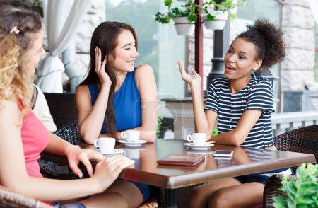 Photo pour Portrait extérieur de trois amies. Filles multiethniques assis dans le café, boire du café et parler. Style de vie urbain et concept d'amitié - image libre de droit