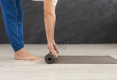 Photo for Unrecognizable man rolling up yoga mat after training. Sport class before or after practicing yoga, preparing for exercise, side view, copy space - Royalty Free Image