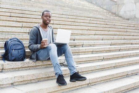 Photo for Happy african-american man with laptop and take away coffee sitting on stairs. Casual student preparing for exams with computer in university campus. Education and technology concept. - Royalty Free Image