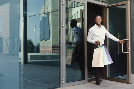 Photo for Happy black man with shopping bags walking out of modern boutique. Successful business and shopping concept - Royalty Free Image