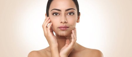 Photo for Beautiful young woman with clean fresh skin touching face . Facial treatment concept - Royalty Free Image