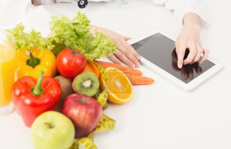 Photo for Female nutritionist working on digital tablet in office. Unrecognizable woman dietitian typing, counting calories or writing diet plan, copy space. Healthy eating concept - Royalty Free Image