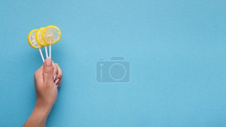 Photo for Fresh citrus lollipops in girls hand. Summer and fun concept, copy space - Royalty Free Image