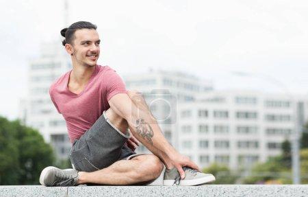 Photo pour Homme tatoué faisant du yoga exercice d'étirement à l'extérieur sur fond de construction - image libre de droit