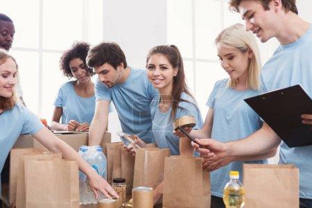 Photo pour Charité de nourriture. Groupe de bénévoles d'emballage don pour sans-abri dans des sacs en papier, travail au bureau, copiez l'espace - image libre de droit