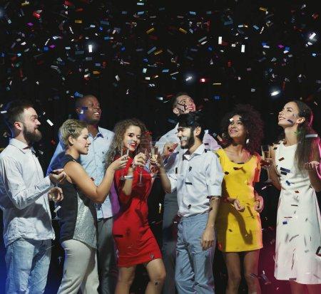 Photo pour Amis heureux anniversaire ensemble au parti sous les confettis - image libre de droit