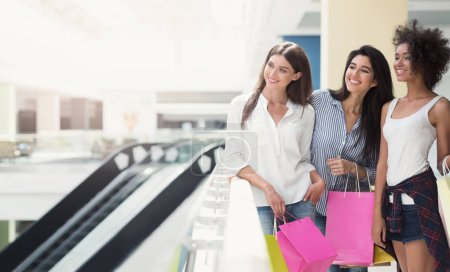 Photo for Happy young women walking in mall with shopping bags - Royalty Free Image