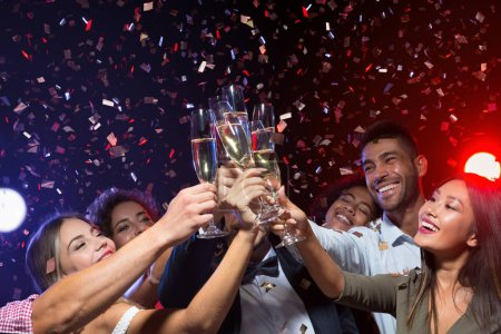 Photo for New year party with friends. Group of cheerful people cheering with champagne flutes, celebrating holiday in club, copy space - Royalty Free Image