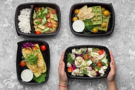 Photo pour Récipients en plastique avec de délicieux plats à emporter sur fond gris, vue de dessus - image libre de droit