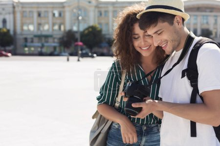 Photo for Tourist couple looking at photos on camera, copy space - Royalty Free Image
