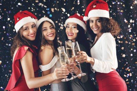 Photo pour Bonne carte de voeux de nouvel an. Quatre femmes heureux pour vous féliciter avec flûtes à champagne - image libre de droit