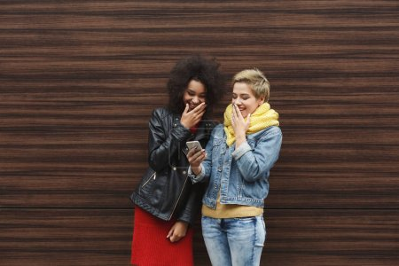 Photo for Surprised multiethnic female friends browsing news on smartphone, while having a city walk, outdoors portrait against wooden wall. Technology, social networks, friendship and urban lifestyle concept - Royalty Free Image