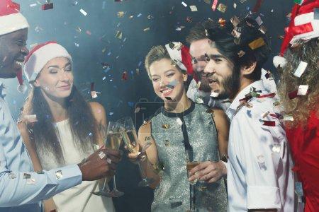 Photo pour Amis multiraciaux cliquetis lunettes tout en célébrant le Nouvel An à la fête - image libre de droit