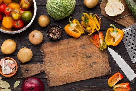 Photo for Preparing vegetarian meal at home. Vegetables assortment on kitchen table with empty cutting board, top view, copy space - Royalty Free Image