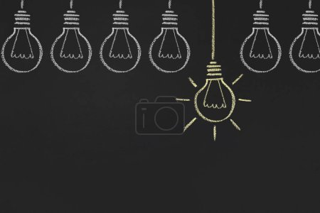 Photo for Inspiration and idea concept. One glowing yellow light bulb between white ones, copy space - Royalty Free Image