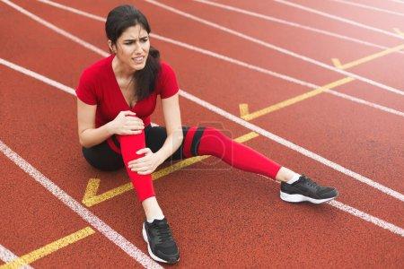 Photo pour Femme avec douleur dans le genou assis sur la piste de course des stades . - image libre de droit