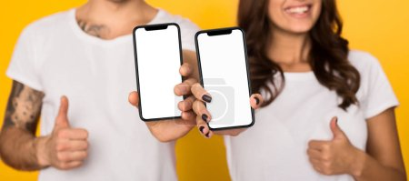 Photo for Couple showing smartphones with blank screens and showing thumbs up against yellow background - Royalty Free Image