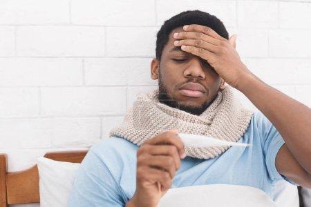 Photo pour Malade homme afro-américain ayant de la fièvre, mesure de la température corporelle avec thermomètre, toucher le front au lit, copier l'espace - image libre de droit