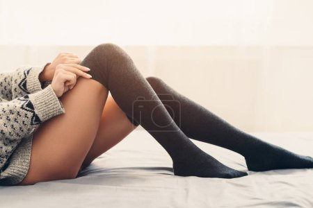 Photo for Young girl putting on long warm stockings in bed, side view, copy space - Royalty Free Image