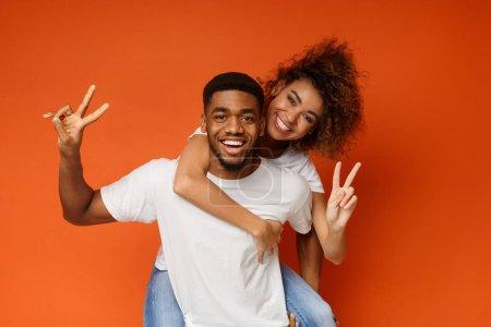 Młody czarny para piggyback jazdy, Wyświetlono ok gest