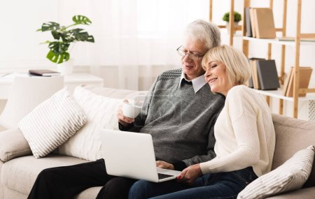 Mature couple browsing internet and drinking coffee