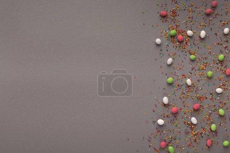 Photo pour Bordure de bonbons colorés et saupoudrer de sucre sur la surface grise. Fond doux pour la publicité de magasin de confiserie, vue de dessus - image libre de droit