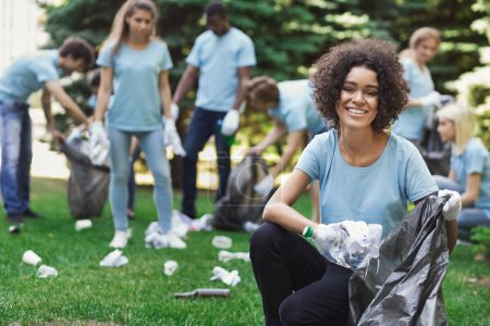 Photo pour Faire du bénévolat, la charité et la notion de salubrité de l'environnement. Heureuse femme noire et le groupe de bénévoles avec garbage bags aire de nettoyage dans le parc, espace copie - image libre de droit