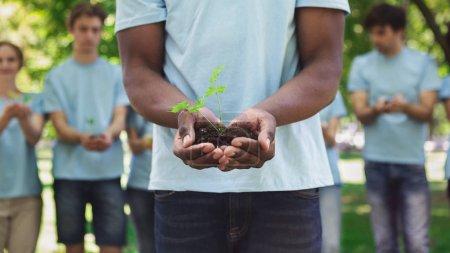 Foto de Caridad, medio ambiente, ecología, agricultura y naturaleza. hombre afroamericano manos sosteniendo planta en el suelo, espacio de copia - Imagen libre de derechos