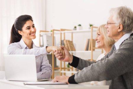 Photo pour Couple de personnes âgées satisfait fabrication vente achat deal, handshaking agent immobilier ou agent immobilier - image libre de droit