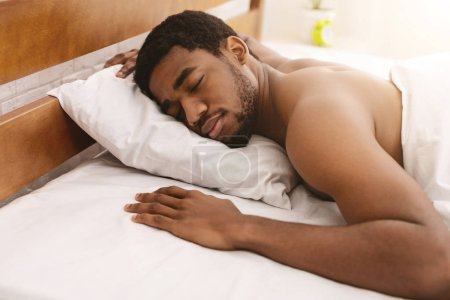 Photo for Comfortable sleep. Naked african-american guy sleeping in bed alone, free space - Royalty Free Image