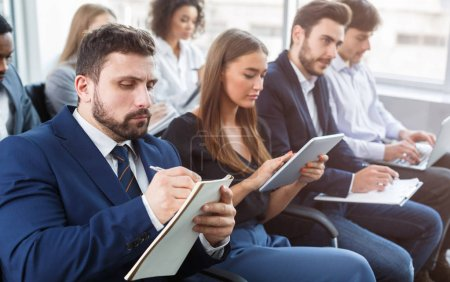 Business training, people making notes at seminar