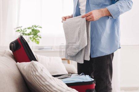 Photo pour Voyage d'affaires. Homme vêtements emballage en sac de voyage, des cultures - image libre de droit
