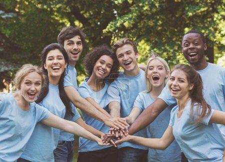 Photo pour Rejoins nous. Jeunes gens divers milléniaux équipe de construction en plein air dans le parc, mettre la main ensemble, copier l'espace - image libre de droit