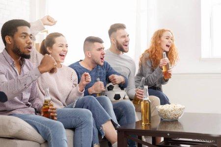 Photo pour Amis applaudir pour l'équipe de football préférée, regarder le match à la maison - image libre de droit