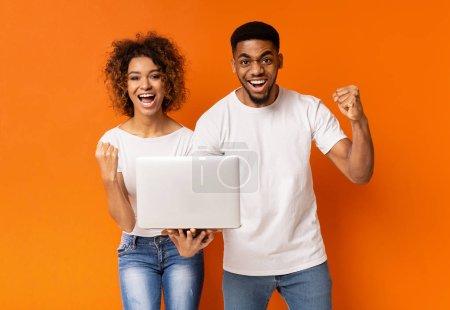 Photo pour Couple millénaire noir excité célébrant victoire avec ordinateur portable, hurlant sur fond de studio orange - image libre de droit