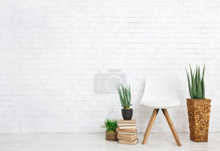 Photo pour Plantes d'intérieur, chaise scandinave et pile de livres sur le plancher au fond blanc de mur de brique, espace de copie - image libre de droit