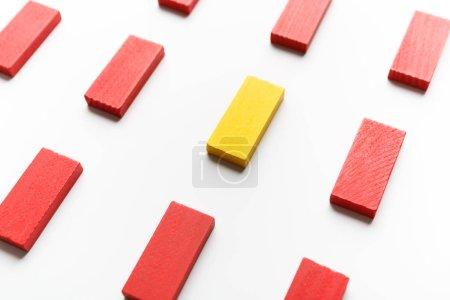 Foto de Individualidad y singularidad. Un bloque de madera amarillo entre los rojos sobre fondo blanco - Imagen libre de derechos