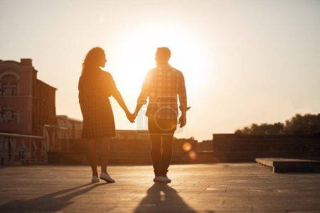 Photo pour Couple tenant la main et marchant dans la rue de la ville au coucher du soleil - image libre de droit