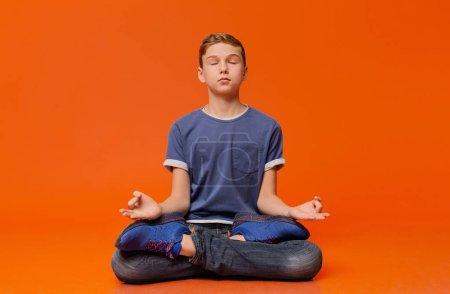 Photo pour Garçon calm assis sur le plancher et la méditation en position du lotus, pratiquer l'yoga, fond de studio orange - image libre de droit