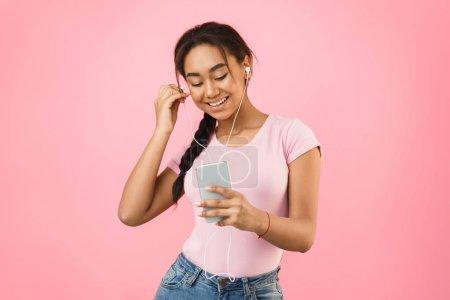Photo pour Jeune fille utilisant le téléphone pour écouter de la musique sur le fond de Studio rose - image libre de droit