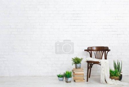 Photo pour Chaise vintage, plantes à la maison et pile de livres sur le sol à fond de mur de briques blanches, espace de copie. Concept de maison confortable - image libre de droit