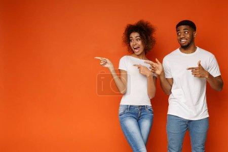 Photo pour Wow Excité homme et femme afro-américain souriant et joyeux pointant de côté à l'espace vide sur fond orange - image libre de droit