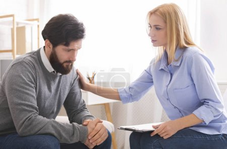 Photo for Professional psychologist comforting sad depressed male patient at personal consultation in office - Royalty Free Image
