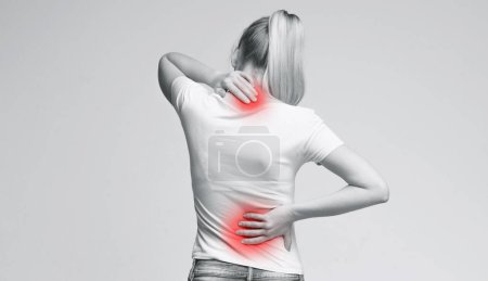 Photo for Woman with neck and back pain, rubbing her painful body, back view, panorama - Royalty Free Image