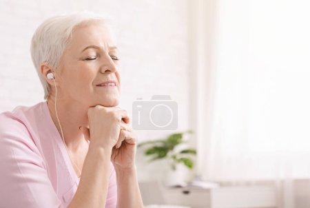 Photo pour C'est l'heure de se détendre. Femme aîné serein appréciant la musique paisible à la maison avec les yeux fermés, l'espace vide - image libre de droit