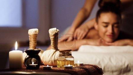Photo pour Massage à base de plantes. Femme détendant dans le salon de spa avec la composition de Spa sur le premier plan - image libre de droit