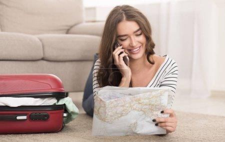 Photo pour Discutez de l'itinéraire. Femme heureuse parlant au téléphone, regardant la carte à la maison - image libre de droit