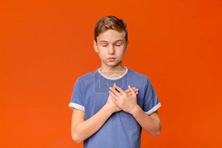 Photo pour Adolescent sensible touché pressant des mains à la poitrine étant reconnaissant, fond orange de studio - image libre de droit