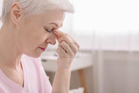 Photo pour Femme aîné fatigué massant le pont de nez, sentant la contrainte d'oeil ou le mal de tête essayant de soulager la douleur, pensant aux problèmes, espace vide - image libre de droit