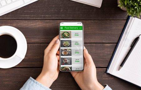 Photo pour Service à emporter. Écran de smartphone à défilement des mains avec application de livraison de nourriture, choix du repas pour le déjeuner, menu déroulant sur le lieu de travail - image libre de droit